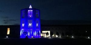 Picture of the Moller Institute Tower illuminated blue for the NHS