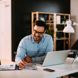 Picture of Young business man working at home with laptop and papers on desk