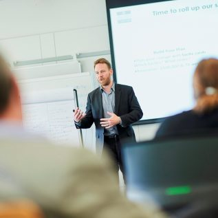 man presenting at an education event at the Moller Centre